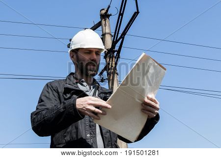 Engineer check electrical systems talk walkie-talkie, Inspector holding blueprints plan.