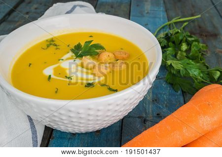 Carrot soup with cream and parsley on wooden background. Copy space