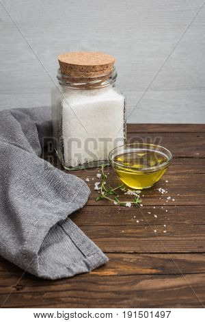 Olive oil with thyme and salt flower on wooden background.
