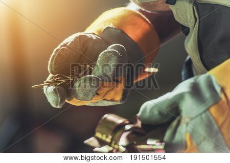 Construction Right Screws in Contractor Hands. Closeup Photo. Building Concept.