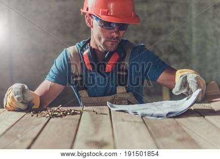 House Construction Contractor with Installation Documentation on the Wooden Table. Construction Worker Reviewing Docs.