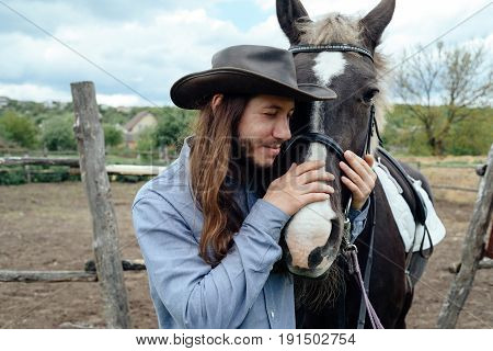 Young Man With Long Hair In Hat Holding Horse's Muzzle On Countryside