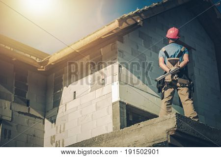 Caucasian Project Manager Supervising House Construction. Construction Site Supervisor Taking Look on the Building From Outside. Residential Construction.