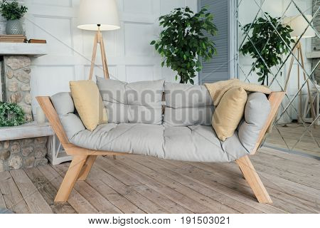 Wooden bench with cushions for relaxing. Interior living room in rustic style
