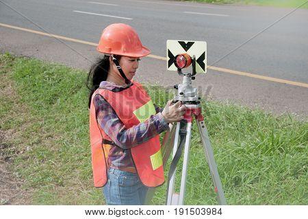 Female Surveyor or Engineer making measure by prism reflector on the highway.