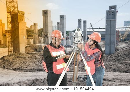 Surveyor or Engineer with partner making measure by Theodolite on the building construction site.