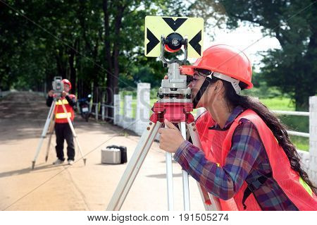 Surveyor or Engineer making measure with partner by Theodolite and prism reflector on the field.