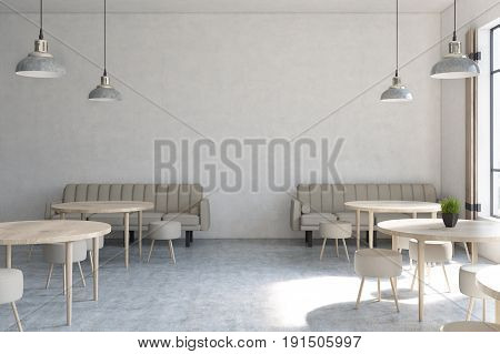 Front view of a modern cafe interior with concrete walls wooden floor round tables and chairs and beige sofas near tall windows. 3d rendering mock up
