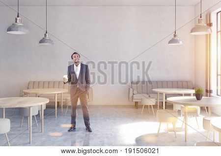 Front view of an African American man in a modern cafe with concrete walls wooden floor round tables and chairs and beige sofas near tall windows. 3d rendering mock up toned image