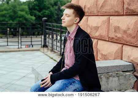 Quiet serene young man in plaid shirt and jacket listening to music with headphones from cell phone outdoors. Student with closed eyes sitting with smart phone and headphones
