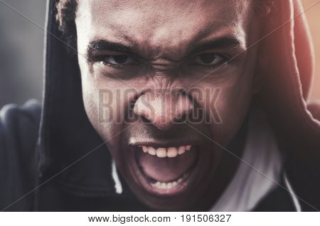 Close up portrait of an angry African American man wearing a hoodie and screaming in anger. Concept of strong emotions. Toned image