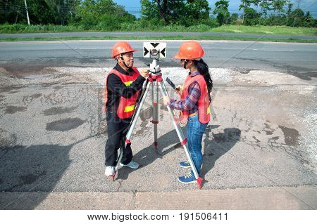 Surveyor or Engineer making measure with partner by prism reflector on the field.