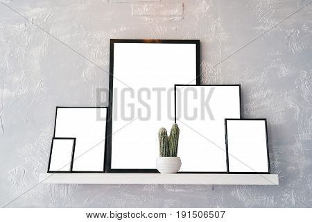 Blank empty white cards with space for text in wooden photo frames. White pot with cactus and photo frames on white shelf on grey background. Blog website social media concept free space