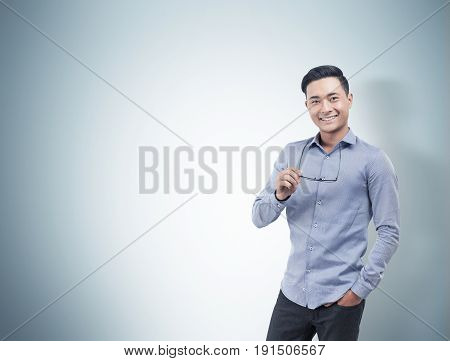 Portrait of a smiling Asian businessman wearing a blue shirt and dark trousers and holding glasses. Concept of success and happiness. Gray background. Mock up