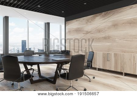 Corner of a light wooden wall decoration and a large round meeting room table. 3d rendering mock up
