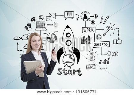 Portrait of a blond businesswoman holding a black marker and standing near a gray wall with a start up rocket sketch drawn on it