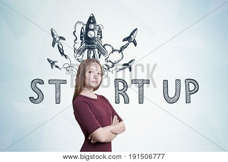 Portrait of a young woman with fair hair wearing a dark red dress and standing with crossed arms. Gray wall colorful start up rocket sketch