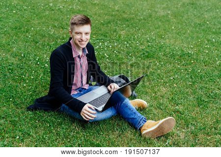 Yong smiling man in plaid shirt and jacket sitting on green lawn on campus reading working on laptop computer. Student studying with laptop computer on knees outdoors