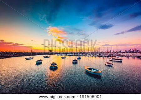 Yachts anchored in a row at St. Kilda beach at sunset Victoria Australia