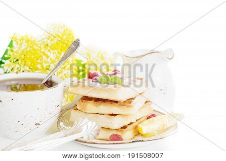 Cup of tea and pile of waffles with raspberries isolated on a white background