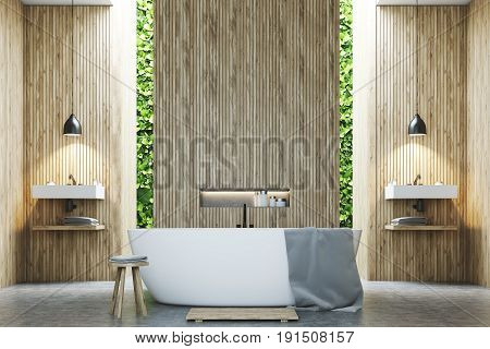 Eco bathroom interior with two narrow windows green shrubbery is seen through them. There are two sinks by the sides of a white tub standing near a wooden wall. 3d rendering mock up