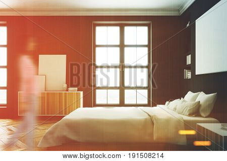 Side view of a modern luxury bedroom with black walls a large bed in the center of the room a bookcase a large window and a framed horizontal poster. Woman. 3d rendering mock up toned image