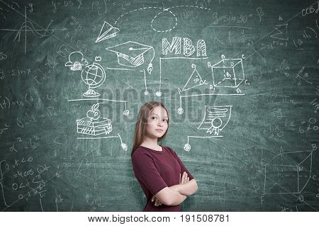 Portrait of a young woman with fair hair wearing a dark red dress and standing with crossed arms. Green chalkboard MBA sketch