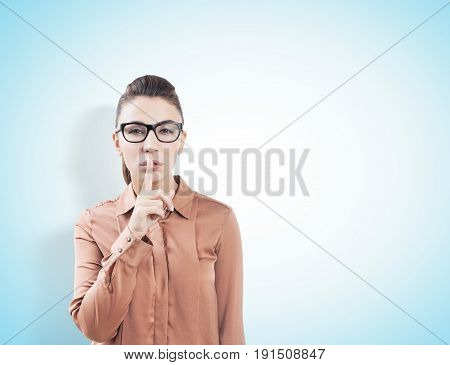 Close up of a young European woman with brown hair making a hush sign. She is standing against a light blue background. Mock up