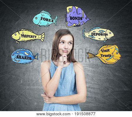 Portrait of a pretty young woman wearing a blue dress and looking sideways. She is standing near a blackboard with colorful fish with stock market buzz words