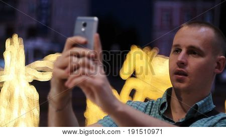 Man taking photo with camera phone at night. Young casual man taking picture with camera phone on the street.
