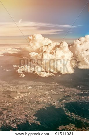 View of clouds and land from airplane window from a height. The vertical frame.