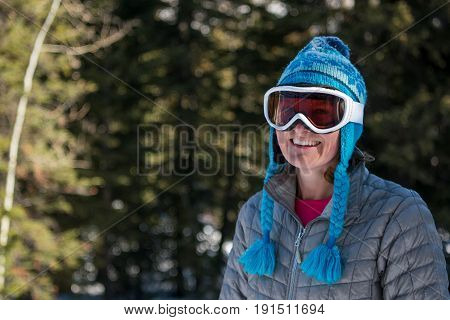 Woman in Toque and Ski Goggles Smiles at Camera in wintery forest