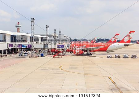 BANGKOK, THAILAND - APRIL 13, 2017: Airplanes docked in Don Mueang International airport at cloudy sky with building on April 13, 2017 in Bangkok Thailand.