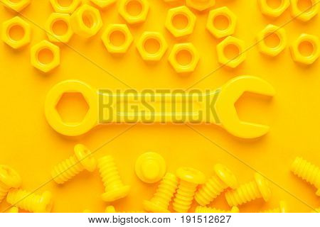 3d printed bolts nuts and wrench on yellow background