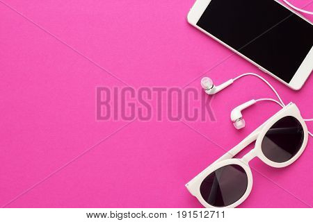 studio shot of white accessories. sunglasses, smart phone and earbuds everyday accessories on magenta background. unisex white accessories on bright pink background. white accessories over purple back with copy space.