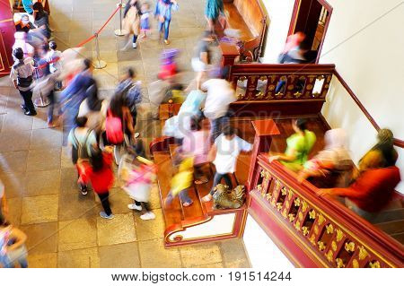 Group of people walking down from the second floor to the first floor through the wooden stair in a historical building in Old Town Jakarta Indonesia. Low speed shutter photography effect.