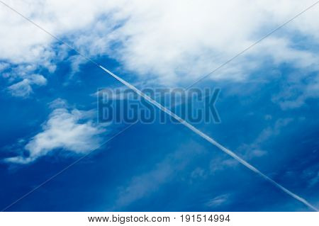 Long contrail from aviation engine in the blue sky. Contrail is a phenomena which made from condensationed hot gas that produced from the aviation engine which fly high at the thin cool air layer in atmosphere.