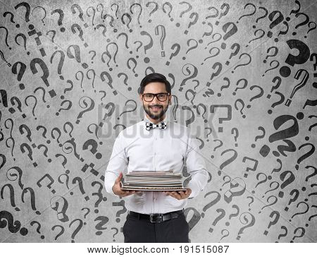 Portrait of businessman holding files in front of wall with question marks
