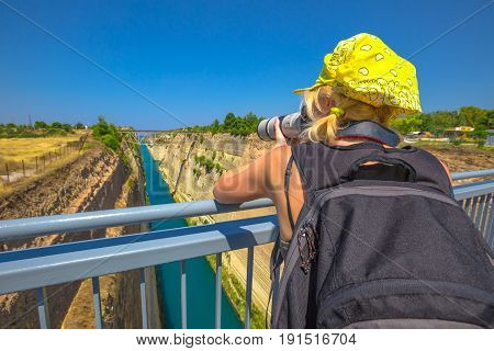 Travel photographer with telelens takes photos from Bridge of Corinth Channel. Corinth Canal connects the Gulf of Corinth with the Saronic Gulf in Aegean Sea. Female photographer in Greece, Europe.