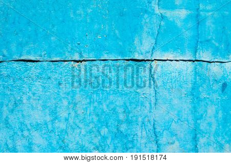 Cracked paint on old metal texture. Blue color. Rusted surface. Joint of steel sheets