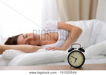 Alarm clock standing on bedside table has already rung early morning to wake up woman in bed sleeping in background. Early awakening, not getting enough sleep, oversleep, time line concept.