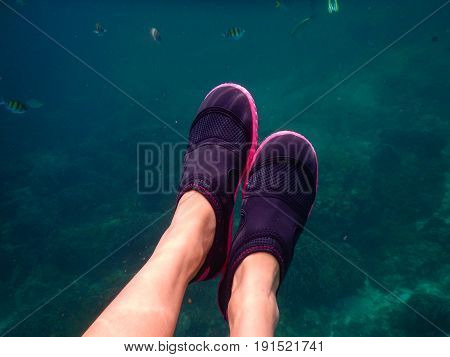 Foot Of Woman Wearing Shoes Snorkeling Under Sea And Have Little Fish Diving Around Her. Coral Putti
