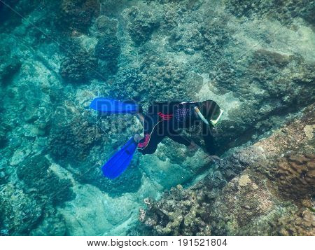 Man Wearing Diving Suit And Dive Goggle. He Diving Snorkeling Under Sea For Checking Coral Condition