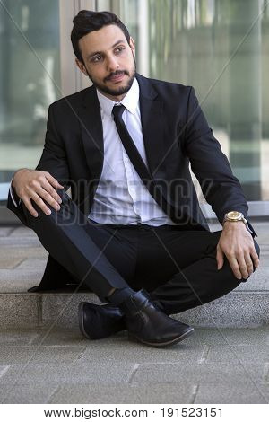 handsome businessman sitting outside on the curb and waiting