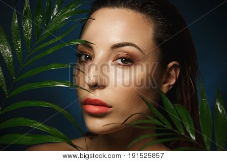Young gorgeous woman with wet slicked back hair standing under exotic plant looking straight.