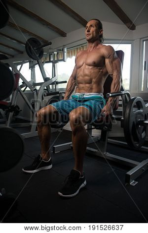 Bodybuilder Exercising Trapezius On Machine