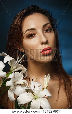Closeup portrait of young amazing woman stading shirtless behind tender flowers. Fashion photography. Nude style.