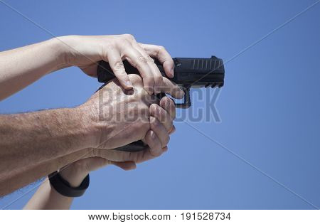 Instructor showing a different way to grip a semi auto pistol