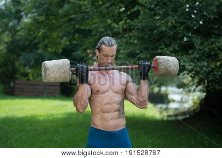 Man Exercise With Made Hand Barbell Outdoors Workout