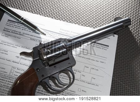 Revolver and pen on the paperwork required for a firearm transfer